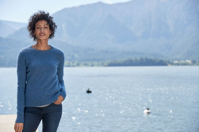 Woman in blue Pendleton sweater stands in front of lake