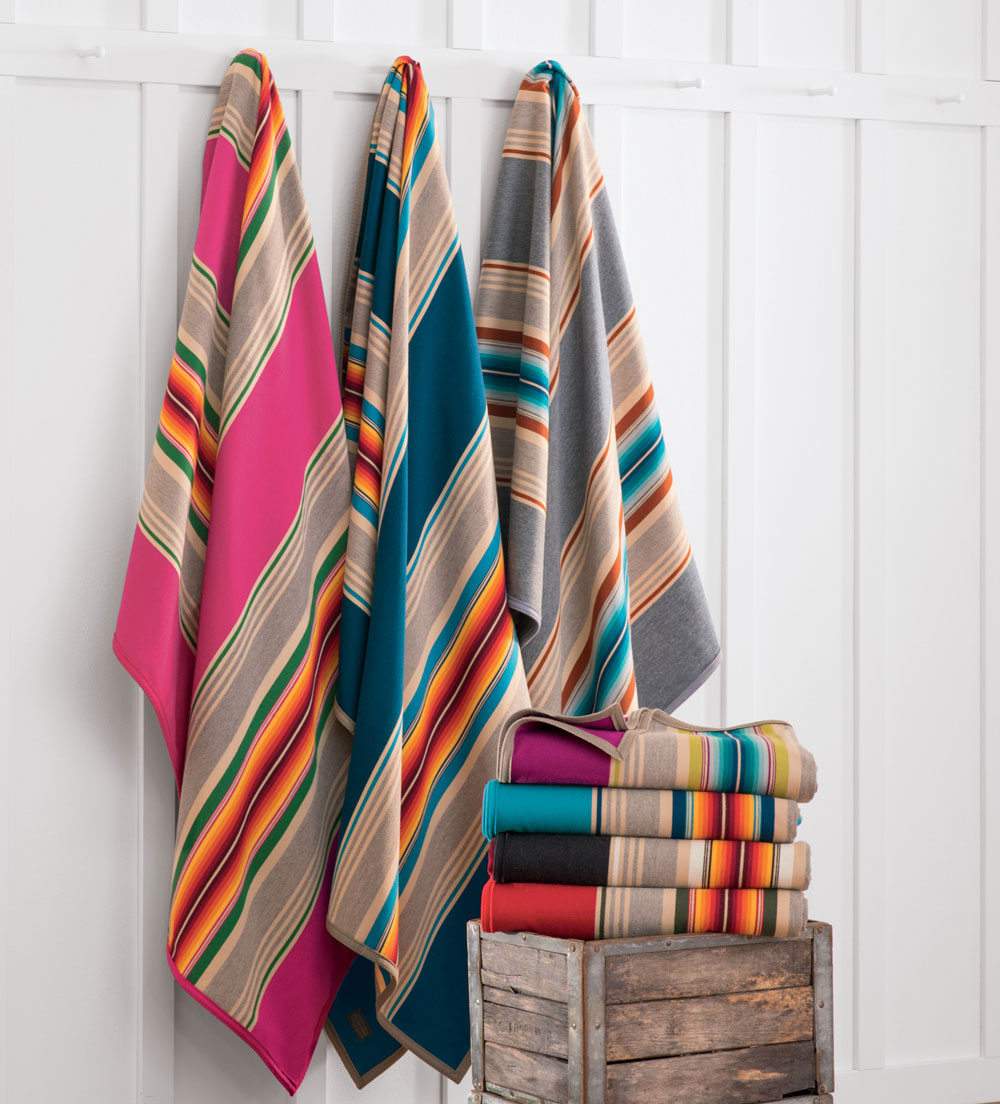 Pendleton serape stripe blankets hanging on pegs, next to a stack of folded Pendleton serape stripe blankets