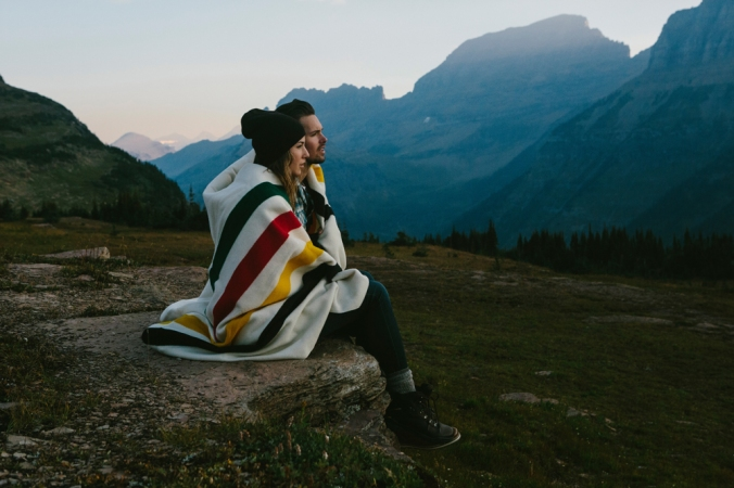 Photo taken in Glacier National Park of a man and woman in front of a glacier, wrapped in a Pendleton Glacier National Park blanket