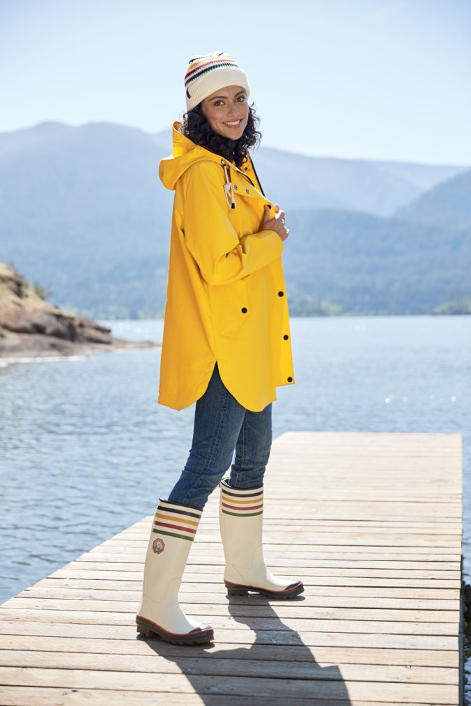 woman in Pendleton rain slicker and boots standing on a dock by a lake.