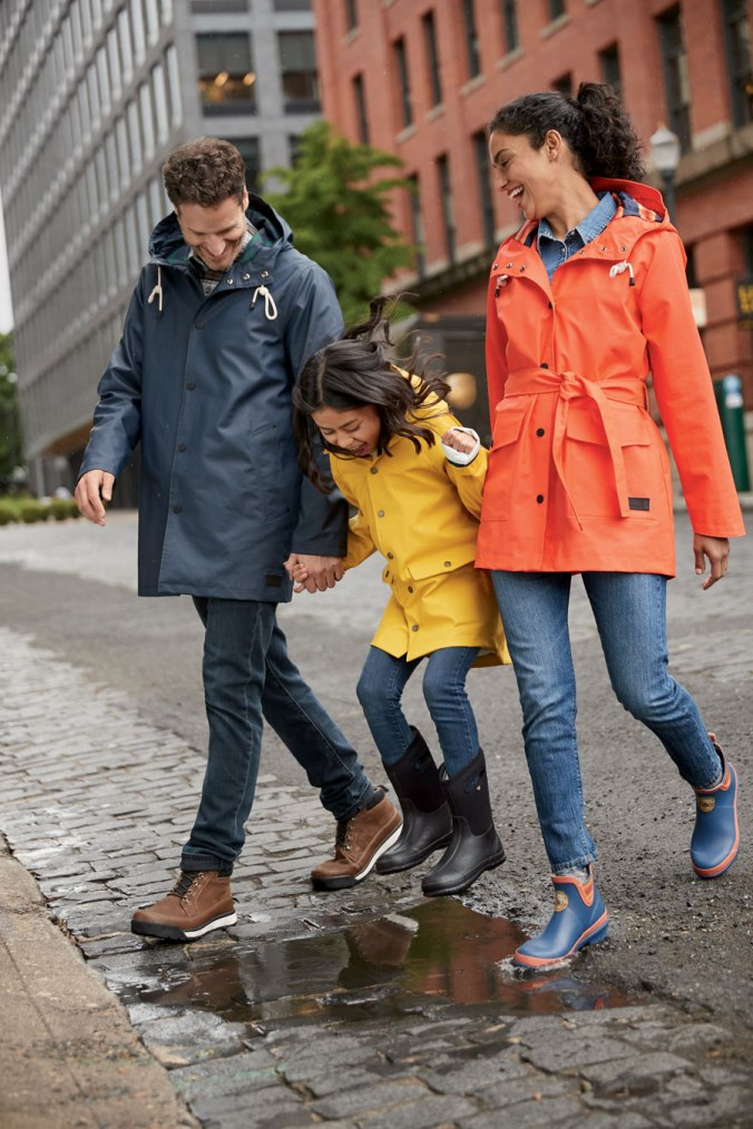 A man, a child, and a woman crossing a cobblestone street wearing Pendleton rain coats.