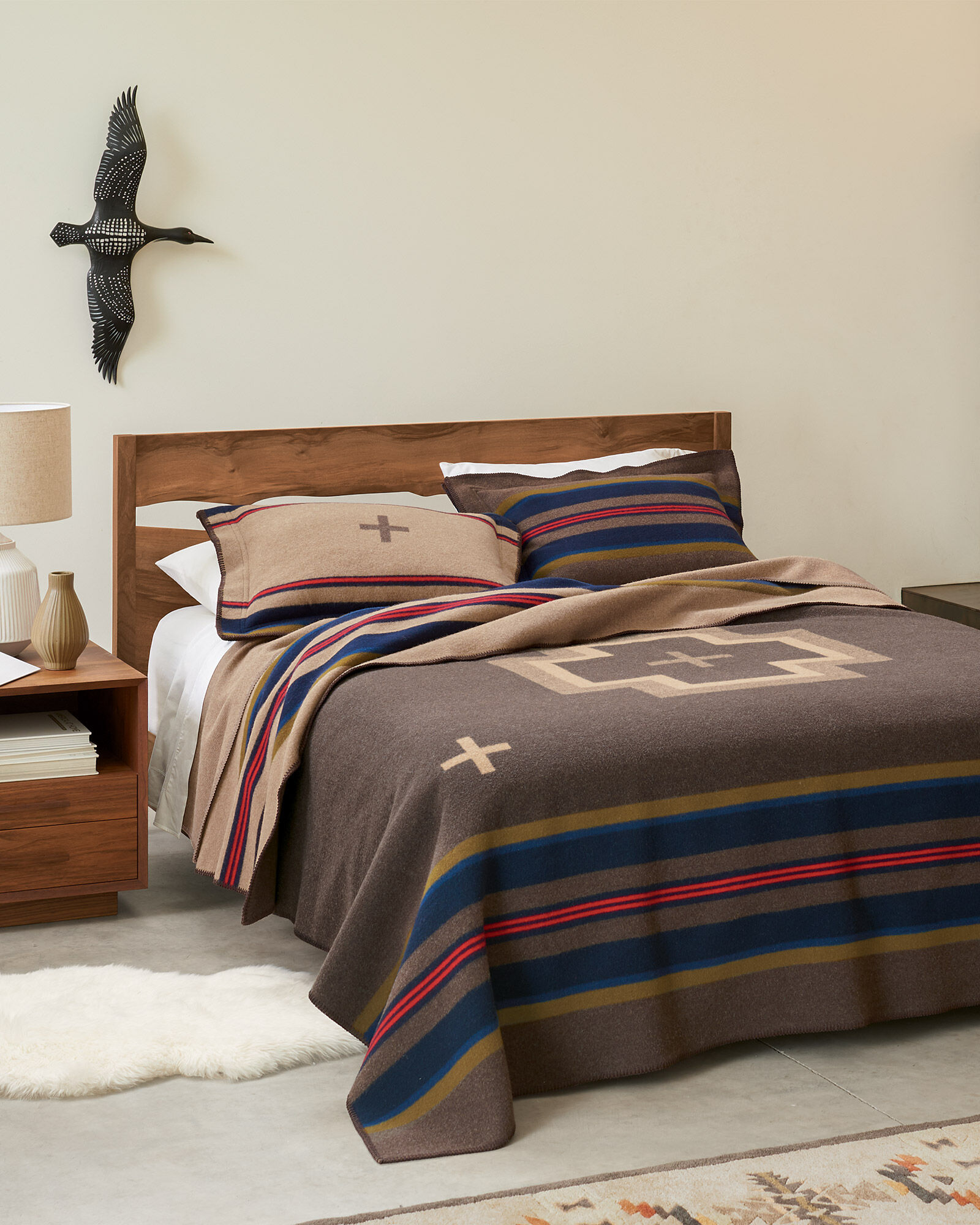 Bed with Shelter bay Pendleton blanket. Blanket is brown with navy, tan and red stripes, and large tan central cross, with smaller crossed in corners.