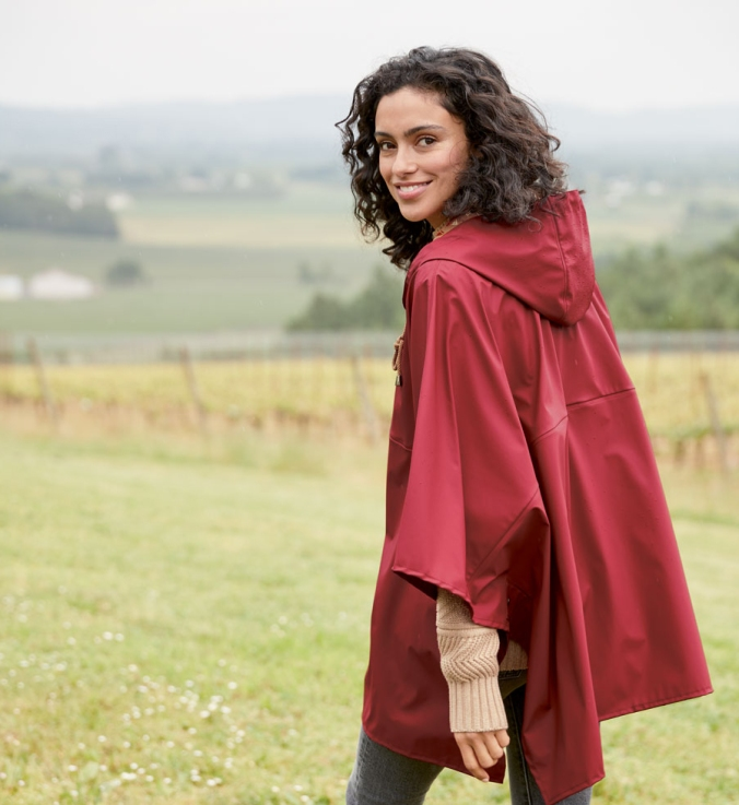 A woman walks in a field wearing a red Pendleton rain poncho.