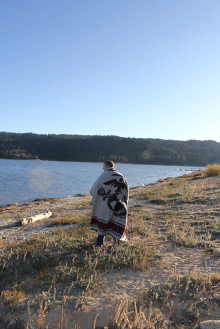 A man stands on the shore of a lake against a bright blue sky, wrapped in a red white and blue Pendleton blanket that features the logo of the United States Marine Corps.