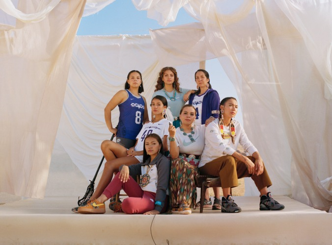 7 Native American women on a raised platform dressed in Nike clothing and shoes.