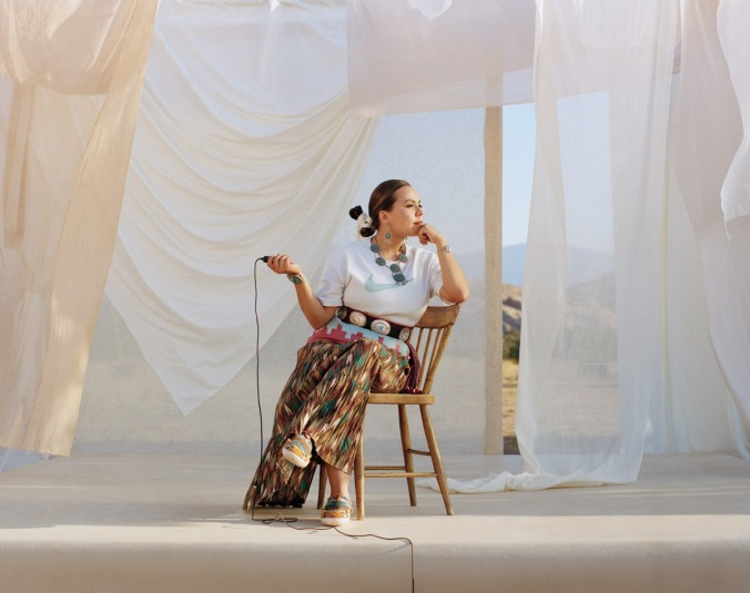 Designer Tracie Jackson sits on a wooden chair on a raised platform against a backdrop of white sheets. She looks to her left, chin in hand. She iw wearing a long skirt, white N7 t-shirt with a turquoise Nike swooshy, and traditional navajo jewelry and concha belt. On her feet she is wearing moccasins from the N7 collection that she designed. In her right hand she holds a shutter button, so she can take the photo herself.