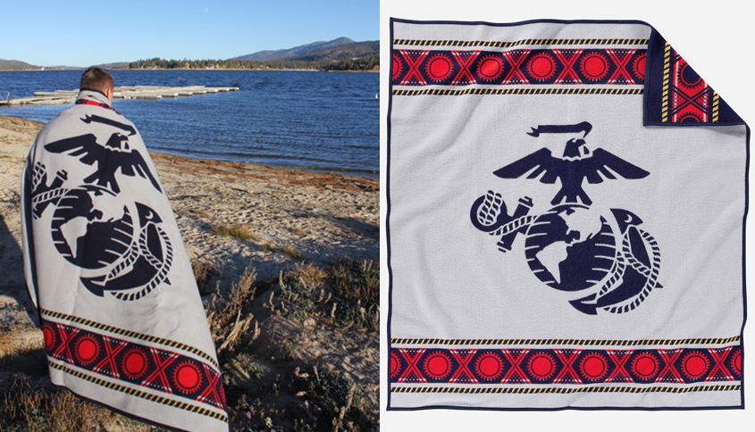 Man stands on shore of lake with USMC blanket.