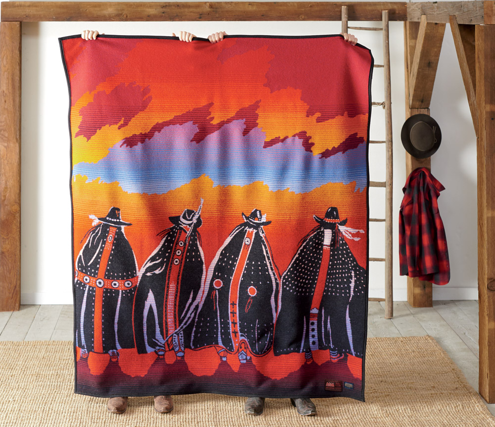 Pendleton Legendary Series blanket, Rodeo Sisters, held up by two people standing behind it.