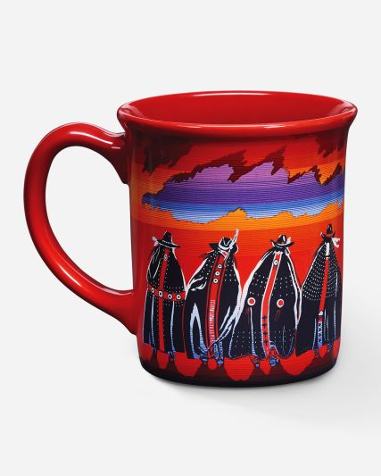 Photo shows the Rodeo Sisters mug, in which eight women ring the mug, all wearing blankets and adorned hats, standing against a fiery sky in reds, oranges and purples.