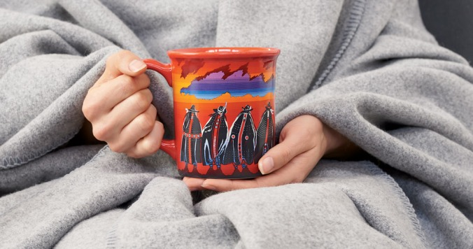 A blanket-wrapped woman's hands holding the Rodeo Sisters mug.