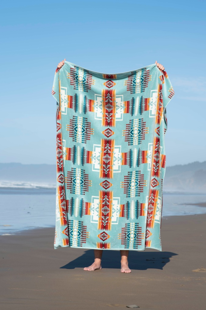 A person stands on a sandy beach holding up a Pendleton Chief Joseph towel.