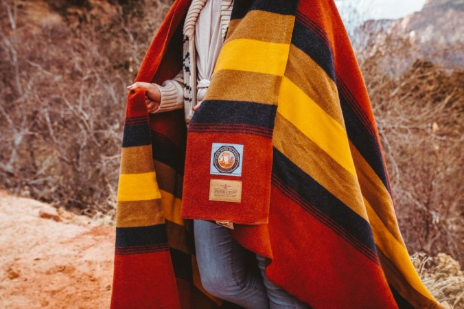 A girl stands in Zion National Park with the Zion blanket around her shoulders.
