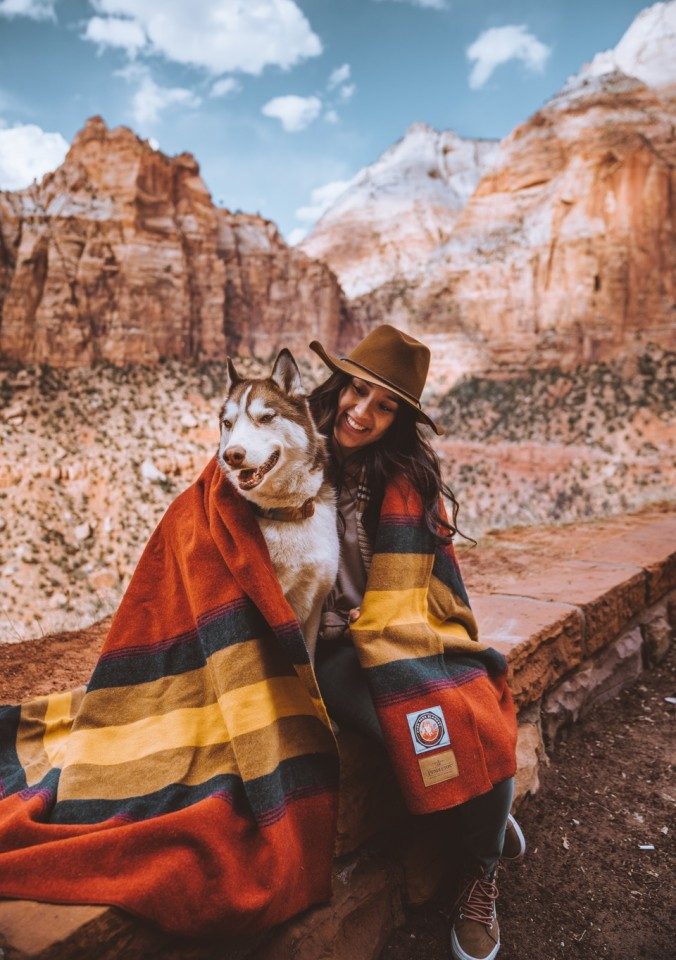 A woman wih a Husky dog sits in Zion National Park wrapped in a Zion blanket.