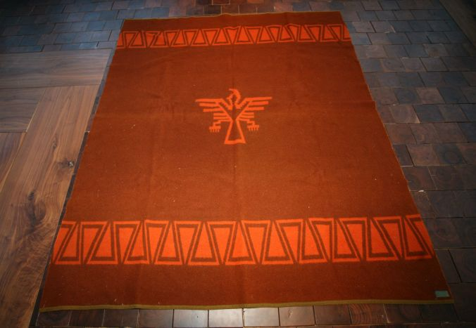 The 1929 version of the Zion Park blanket, a thunderbird on a rust red background.