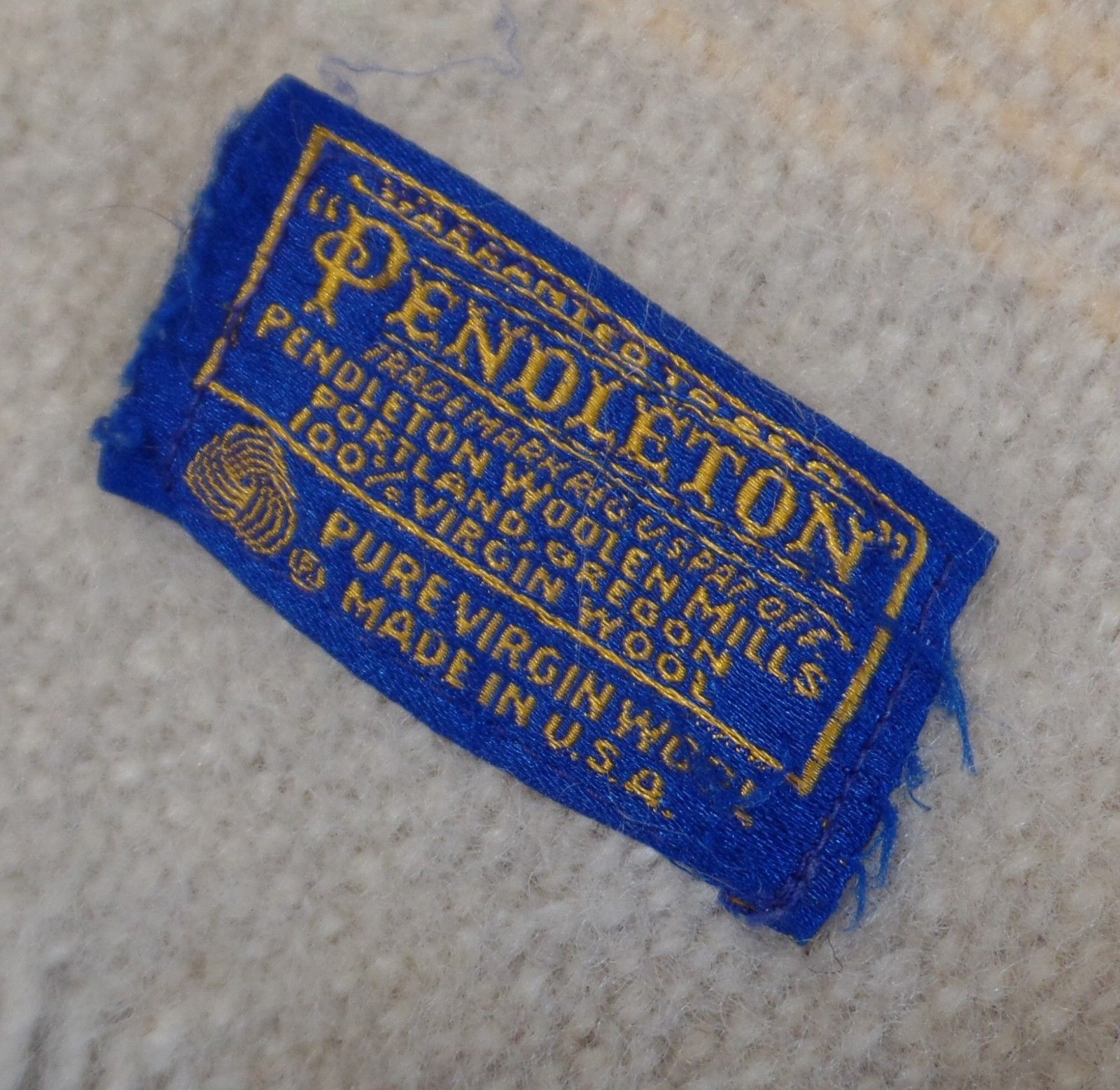 A closeup of the Pendleton blue and gold embroidered label on the 1960s Zion National Park throw.