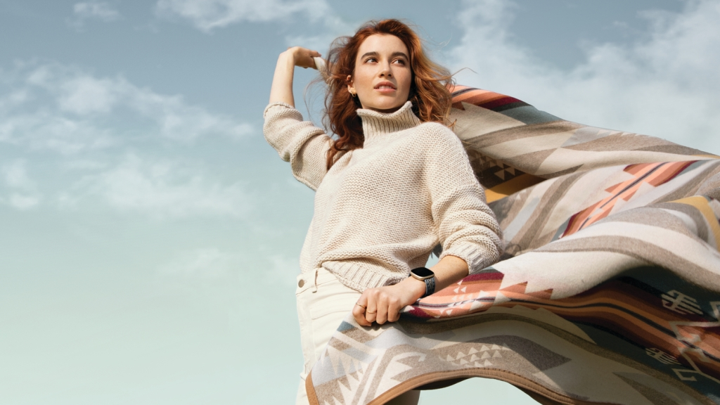 A young woman holds a Pendleton blanket wearing a Pendleton Fitbit device