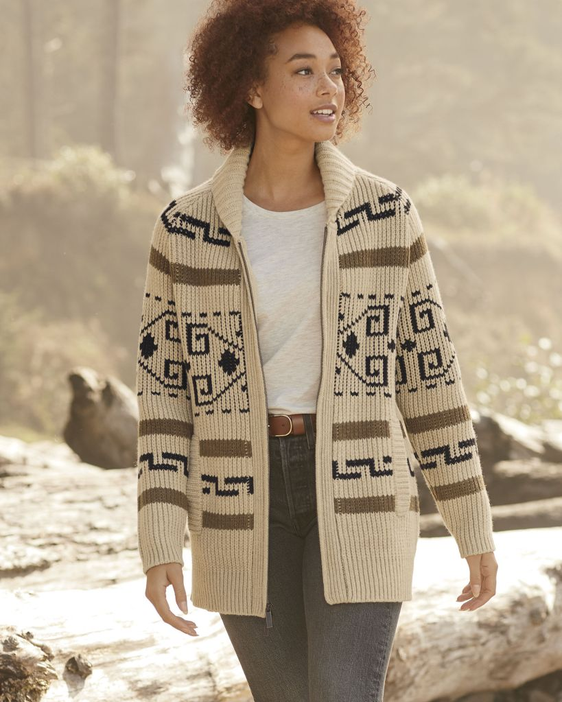 A woman walks on the beach wearing a Westerley cardigan by Pendleton.