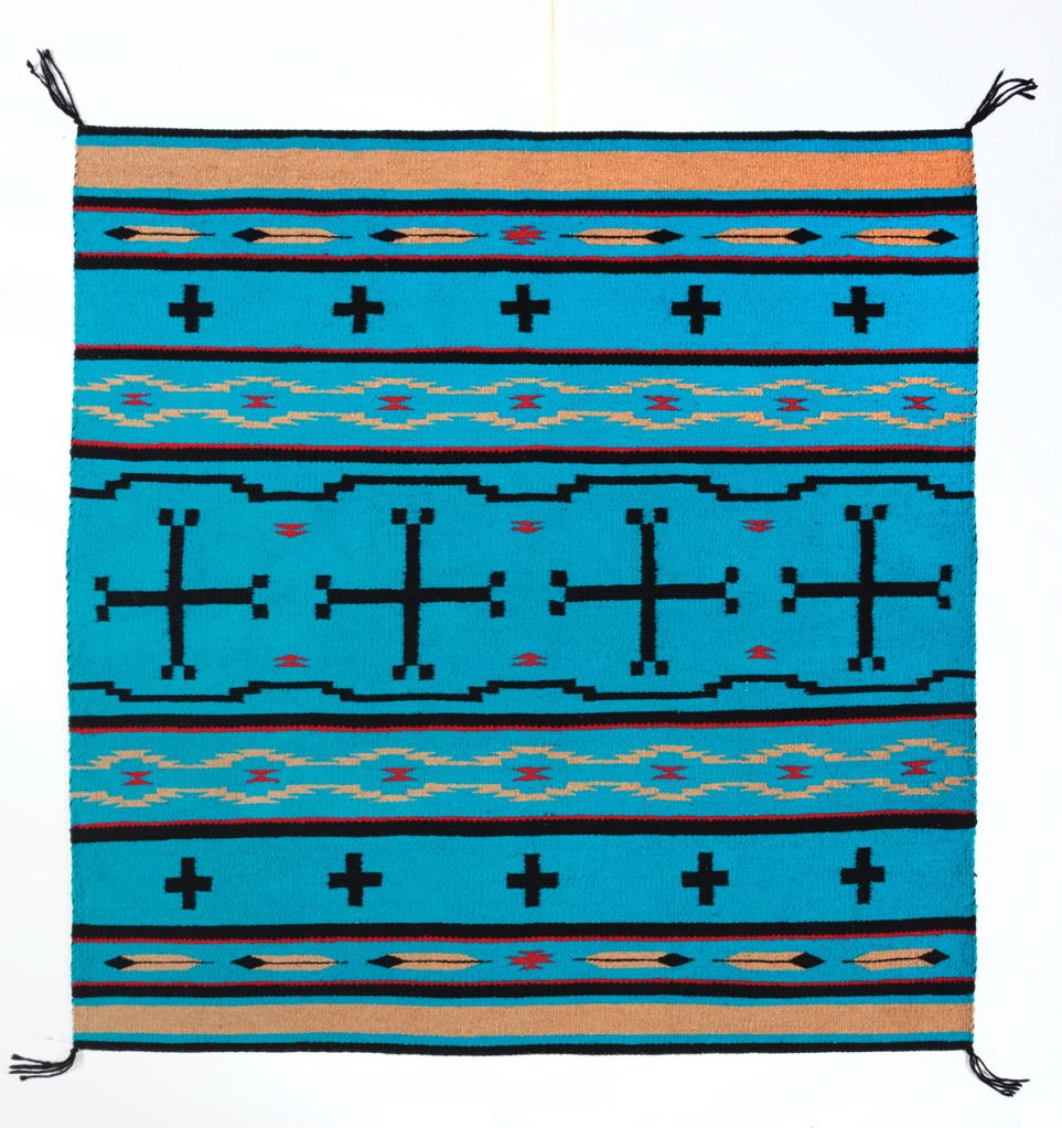 Handwoven rug made by a Navajo weaver in turquoise and black.