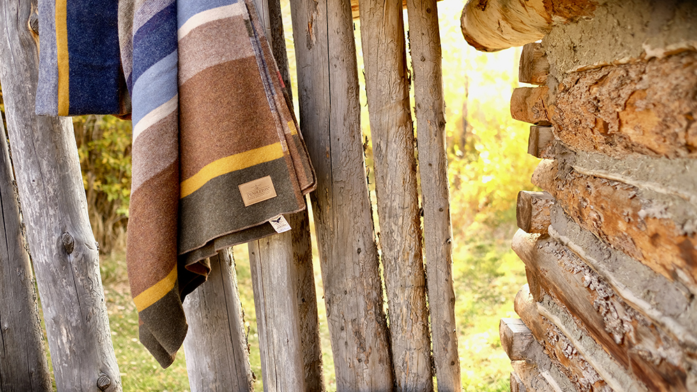 Pendleton Bridger Stripe blanket hanging on a wooden fence at Fort Bridger