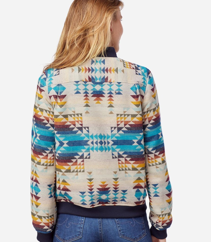 A woman faces away from the camera, she is wearing a jacket in the Pilot Rock pattern