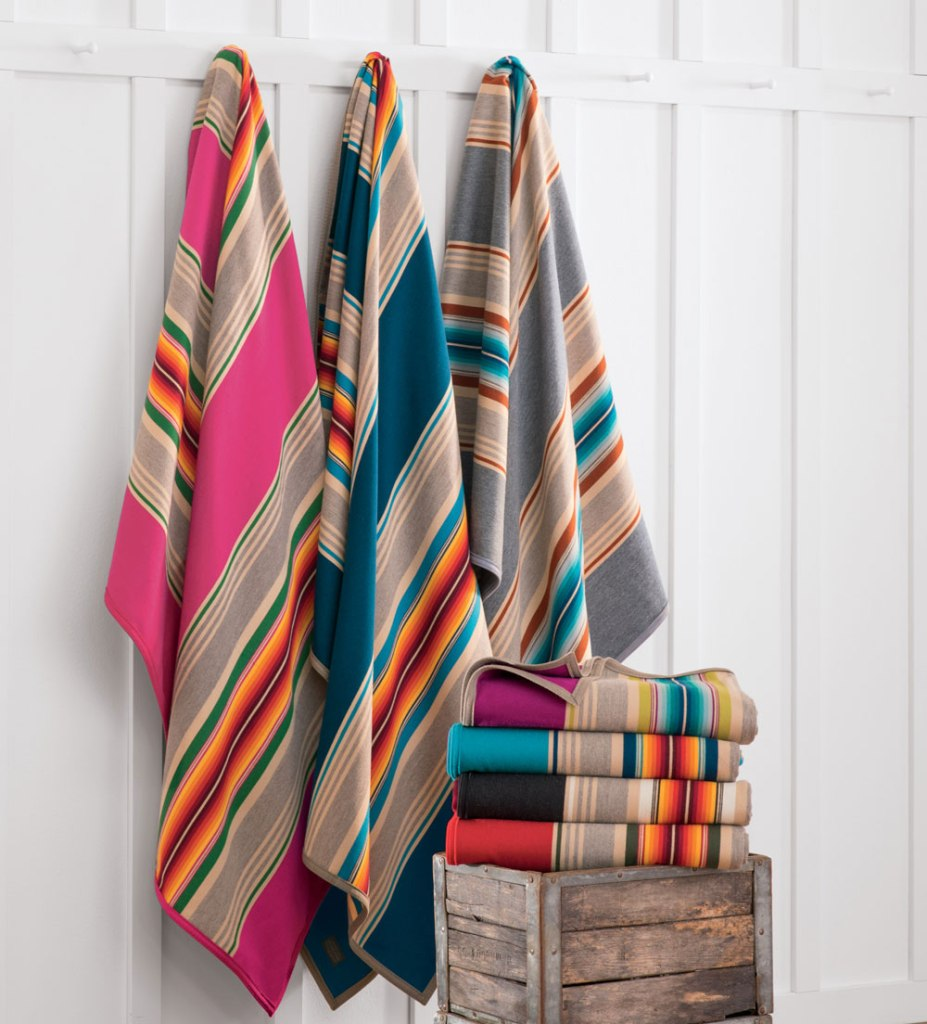 Pendleton serapes hang on pegs in front of a white wall, with more folded on a crate.