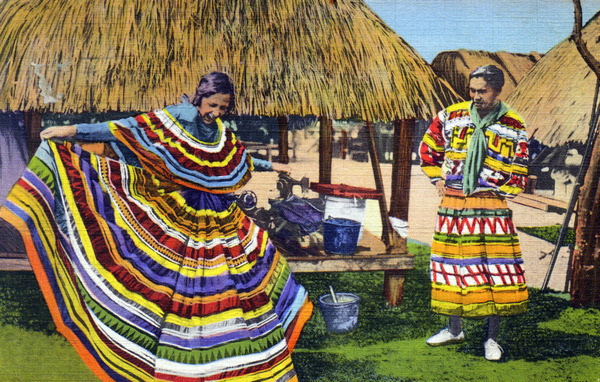 Vintage tourist postcard of a man and woman wearing traditional Seminole strip clothing