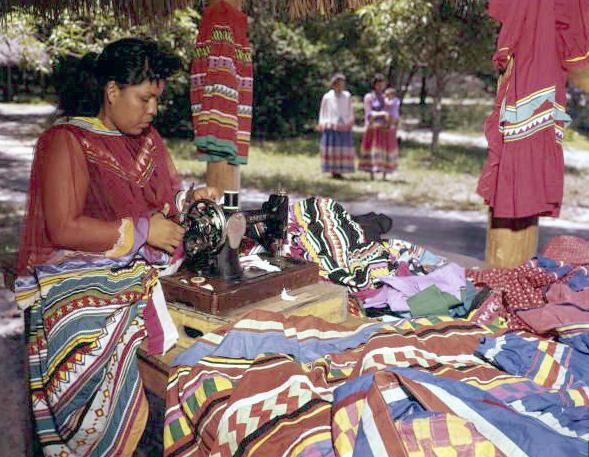 A Seminole seamsress sews garments on a sewing machine