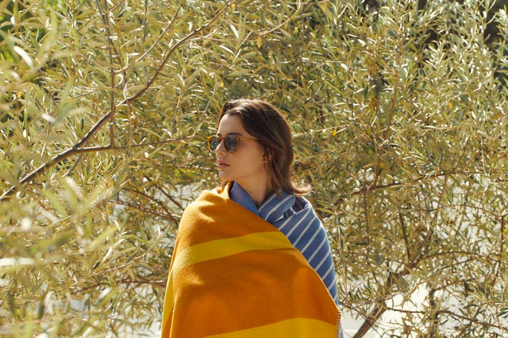 A young woman wrapped in a blanket stands in front of greenery  (photo copyright 2021 GLCO)