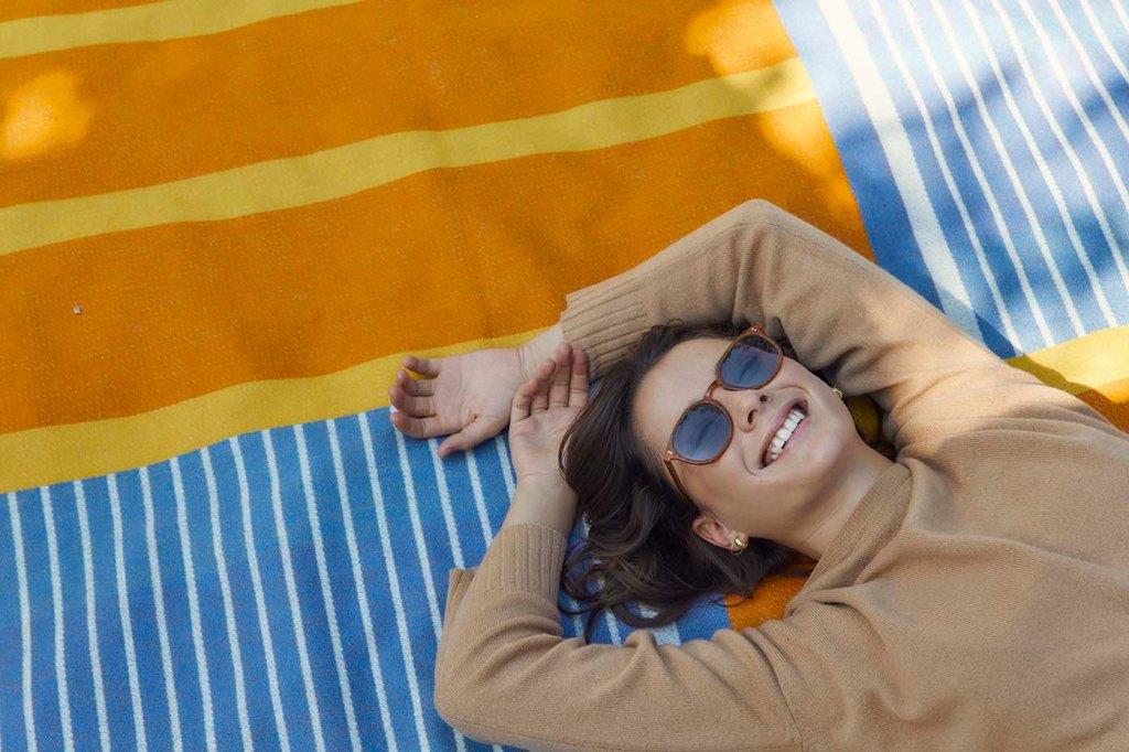 A smiling woman wearing GLCO sunglasses reclines on the GLCO x pendleton blanket  (photo copyright 2021 GLCO)